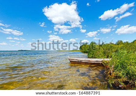 Summer lake view with wooden boat near shore