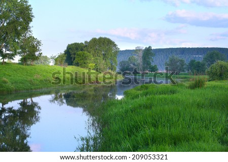summer landscape early in the morning on the river and clouds reflected in the mirrored surface of the water - stock photo