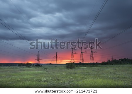 summer landscape high voltage power lines on sunrise background in the field near the woods