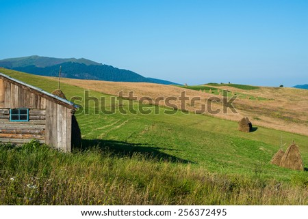 Summer landscape in the Ukrainian Carpathian Mountains with the wooden shed in the foreground, - stock photo