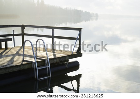 summer landscape, lake and wooden jetty in fog - stock photo