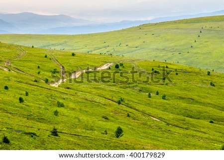 summer landscape. mountain path through the hillside meadow turns uphill to the sky - stock photo