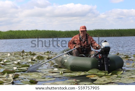 Summer landscape of a fisherman in a boat on the lake with white lilies