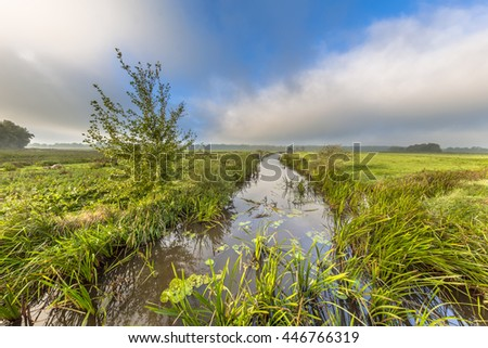 Summer landscape of a lowland river valley in Drenthe with fog opening to low fast travelling clouds and strong headwind near Eelde, the Netherlands - stock photo