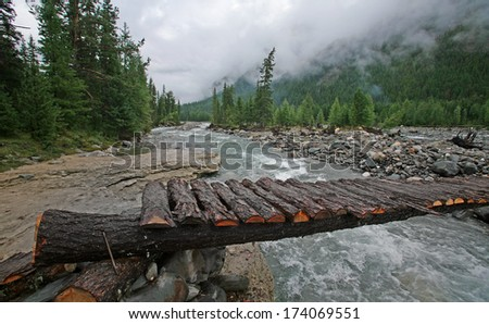 summer landscape of a wooden bridge across the mountain river, pine forests and clouds - stock photo