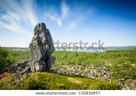"Summer landscape of northern Russia. Kola Peninsula, not far from Murmansk. In the photo the place of worship of the ancient people - ""Stone woman"""