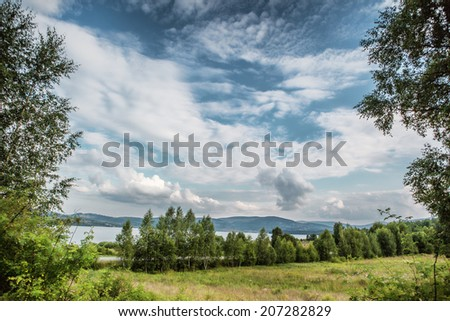 Summer landscape of young green forest with blue sky, clouds and lake - stock photo