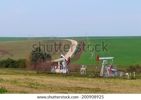 summer landscape oil pumps on the background fields and the road on a sunny day - stock photo