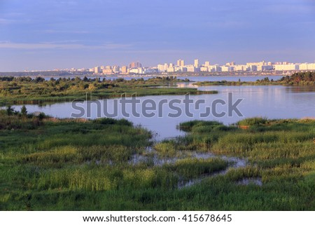 summer landscape river at sunset with a view of the city