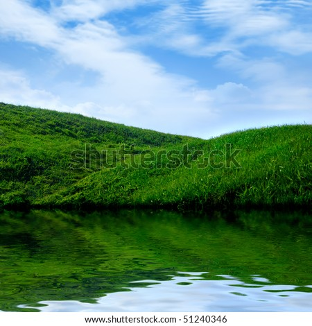 Summer landscape scenery background. Water, green grass and blue sky.