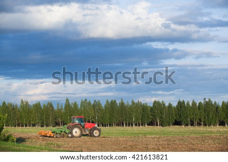 summer landscape tractor in a field plowing land - stock photo