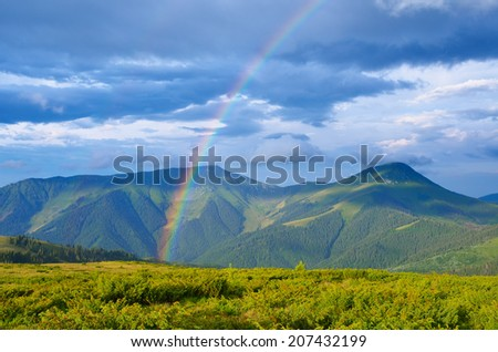 Summer landscape with a rainbow in the mountains. Sunshine after the rain. Beauty in nature - stock photo