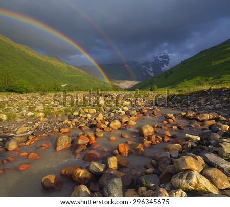 Summer landscape with a rainbow over the mountain river. Beauty in nature - stock photo