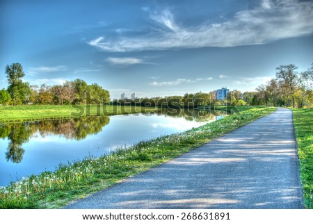 Summer landscape with a road along the river. - stock photo