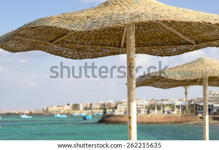 Summer landscape with beach umbrellas on a tropical beach. Resort vacation on a coast. - stock photo