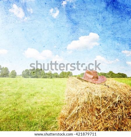 Summer landscape with cowboy hat on haystack - stock photo