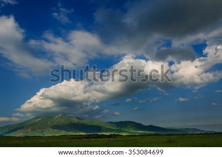 Summer landscape with dramatic clouds - stock photo