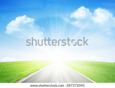 Summer landscape with endless asphalt road through the green field and blue sky - stock photo