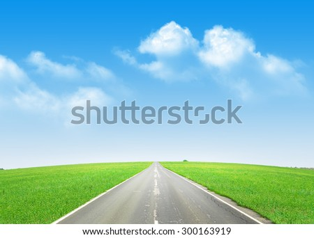 Summer landscape with endless asphalt road through the green field and blue sky