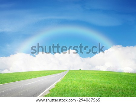 Summer landscape with endless asphalt road through the green field and blue sky with clouds and rainbow  - stock photo