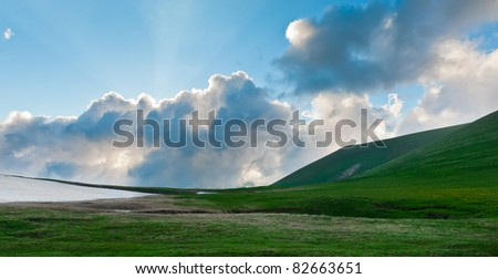 Summer landscape with green grass, mountains and clouds