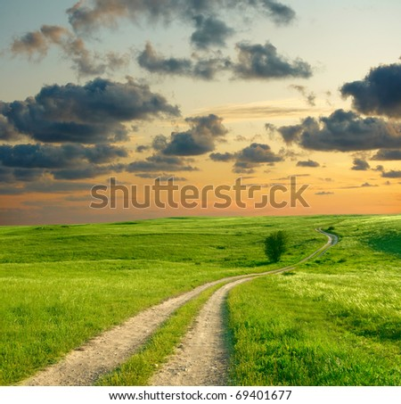 Summer landscape with green grass, road and dramatic sky - stock photo