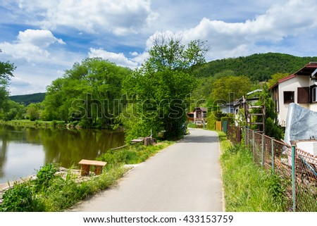 Summer landscape with green grass, road, river and clouds - stock photo