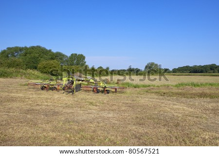summer landscape with hay turning equipment in a newly cut hay field under a clear blue summer sky
