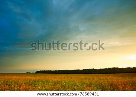 summer landscape with hayfield and storm clouds - stock photo