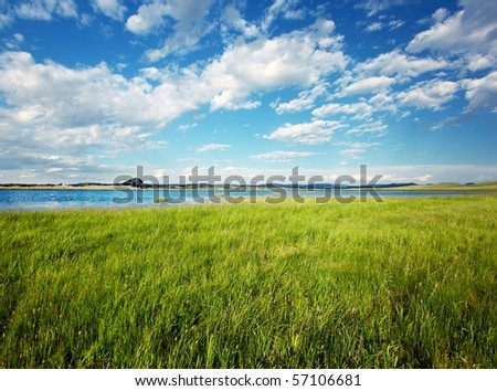 Summer landscape with lake and cloudy sky - stock photo