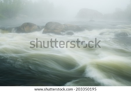 Summer landscape with morning fog over the river. Turbulent stream with cascades between rocks - stock photo