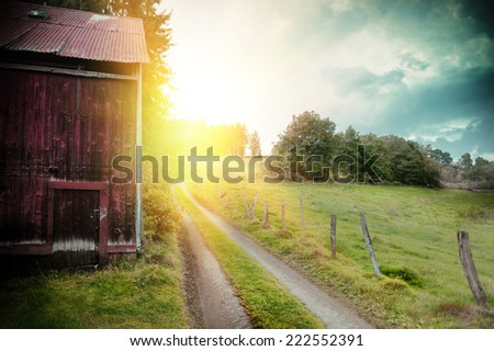 Summer landscape with old barn and country road  - stock photo