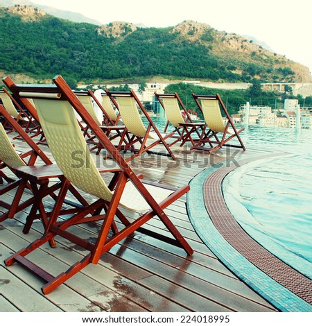 summer landscape with resort swimming pool and outdoor chairs on terrace over Mediterranean sea (Montenegro) - stock photo