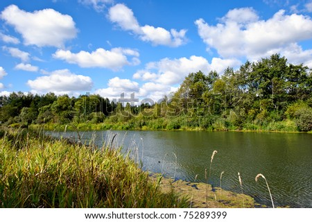 Summer landscape with river and cloudy sky - stock photo