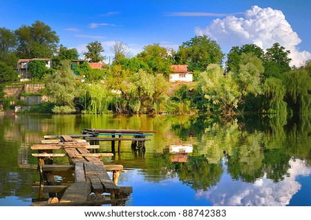 Summer landscape with river and cloudy sky. - stock photo