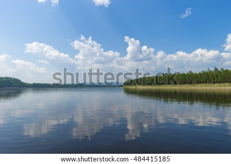 Summer landscape with river, cloudy sky, forest and sun
