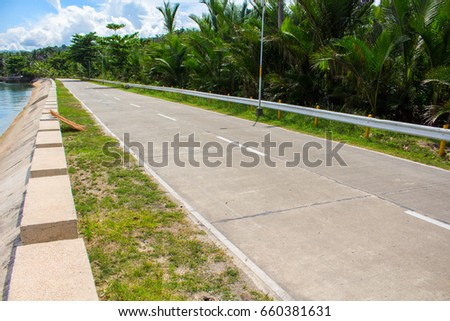 Summer landscape with road and green roadside. Roadtrip in sunny day by sea. Seaside road view. Summer travel poster template. Tropic island journey. Asphalt highway by seaside. Vacation travel drive