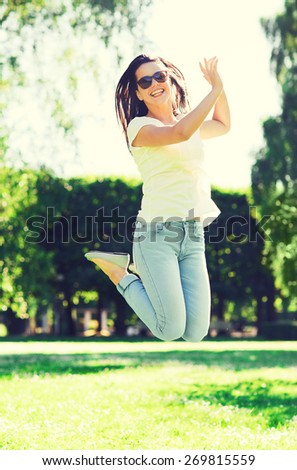 summer, leasure, vacation and people concept - smiling young woman wearing sunglasses standing in park - stock photo