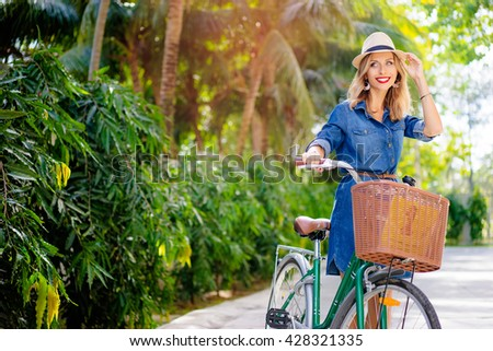 Summer leisure. Pretty young woman in hat walking with bicycle. - stock photo