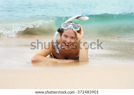 Summer leisure. Young beautiful girl with an underwater mask lies on the beach in the sand close up. Smiling in anticipation of larger wave back.