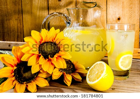 Summer lemonade with lemon slices, pitcher, and sunflowers on wood bench.   - stock photo
