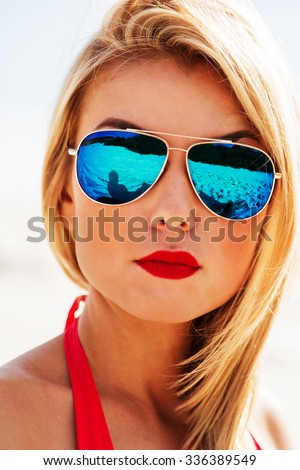 Summer lifestyle close up portrait of stunning woman with tanned fit sexy body, blonde hair and red lips, wearing bright red bikini and sunglasses, posing on the sand. - stock photo