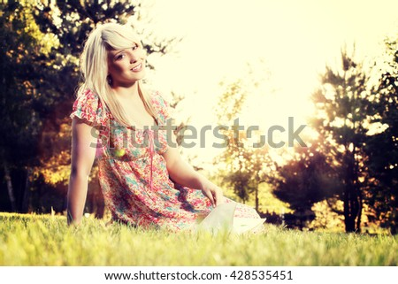 Summer lifestyle concept. Blonde young woman girl relaxing in a park reading book, sitting alone on grass. Sunny day - stock photo