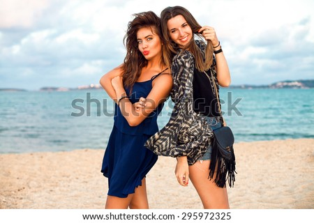 Summer lifestyle fashion portrait of young woman in stylish outfit holding hat and walking near ocean, positive mood,vintage toned colors.Party girls,friends having fun,girls night out,beach party - stock photo