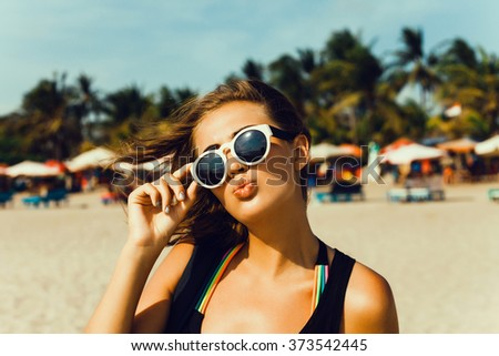 Summer lifestyle happy smiling portrait of pretty young woman blonde fashion having fun on the beach on tropic island in sunglasses,holiday,lipstick,cover,beauty,student,reading,miami beach  - stock photo