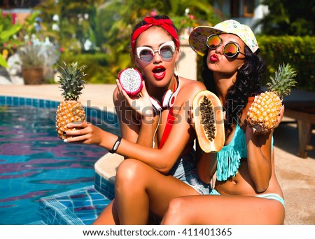 Summer lifestyle happy smiling portrait of two pretty young women blonde and brunette fashion stylish girls having fun on the beach on tropic island in sunglasses and tropical fruits on their hands - stock photo