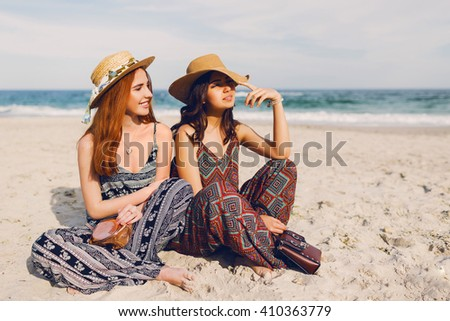 Summer lifestyle image of two cute young women  sitting on the beach , enjoying time together. Wearing bright stylish boho  summer outfit, straw hat.  - stock photo