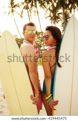 Summer lifestyle portrait of couple in love. Standing back on the sunset background. Holding surfboard. Wearing stylish bikini, bracelets. On honeymoon. Interracial couple, Asian woman, Caucasian man - stock photo