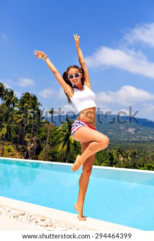 Summer lifestyle portrait of young hipster girl, enjoy her exotic vacation, wearing crop top and sexy shorts, jumping put her hands to the air. - stock photo