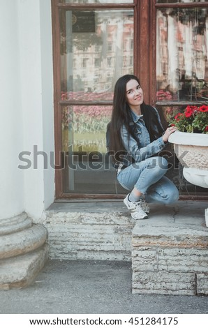 Summer lifestyle portrait of young hipster woman walking, smiling enjoy weekends. Attractive brunette female in casual jeans clothes, sitting near red summer flowers in European city. - stock photo